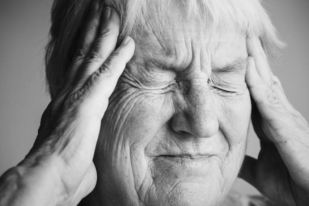 Elderly woman suffering from migraine